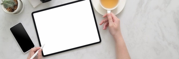 Fotografía cenital de una mujer freelance trabajando en una tableta simulada en una mesa de mármol