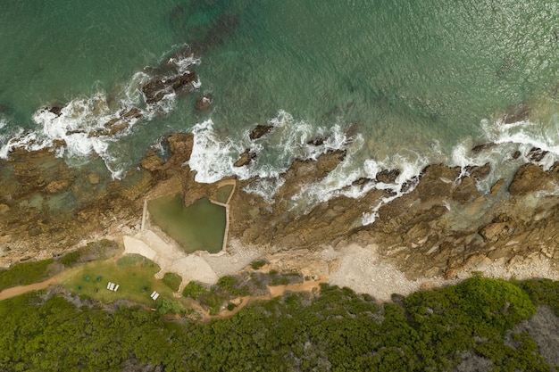 Fotografía cenital de una orilla del mar con agua verde pura durante el día