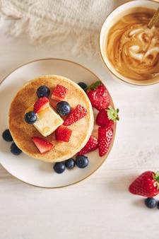Fotografía cenital de panqueques veganos con frutas en el desayuno