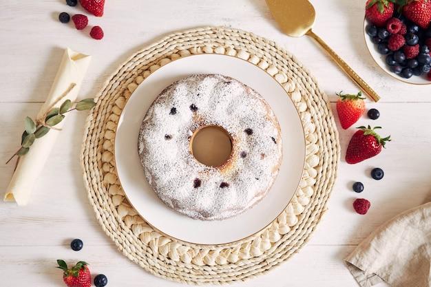 Fotografía cenital de un pastel de anillo con frutas y polvo sobre una mesa blanca