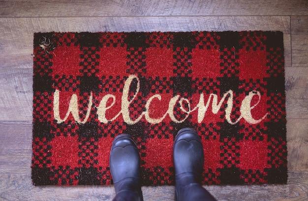 Fotografía cenital de una persona de pie sobre una alfombra de bienvenida