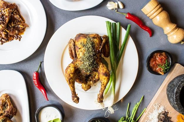 Fotografía cenital de pollo asado en un plato redondo rodeado de guarniciones