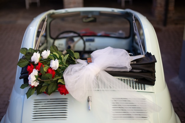 Fotografía cenital de ramo de flores colocado en la parte superior del coche con un fondo borroso