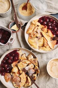 Fotografía cenital vertical de deliciosos panqueques esponjosos con cereza y azúcar en polvo