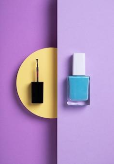 Fotografía cenital vertical de esmalte de uñas azul y un aplicador negro fondo púrpura amarillo geométrico