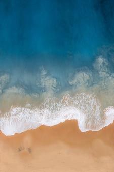 Fotografía cenital vertical de un mar ondulado contra la orilla del mar