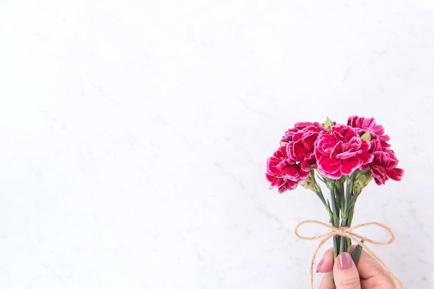 Fotografía del concepto de la idea del día de las madres de mayo - hermosos claveles florecientes atados con un arco de cuerda que se sostiene en la mano de la mujer aislada en la mesa moderna y brillante, espacio de copia, endecha plana, vista superior