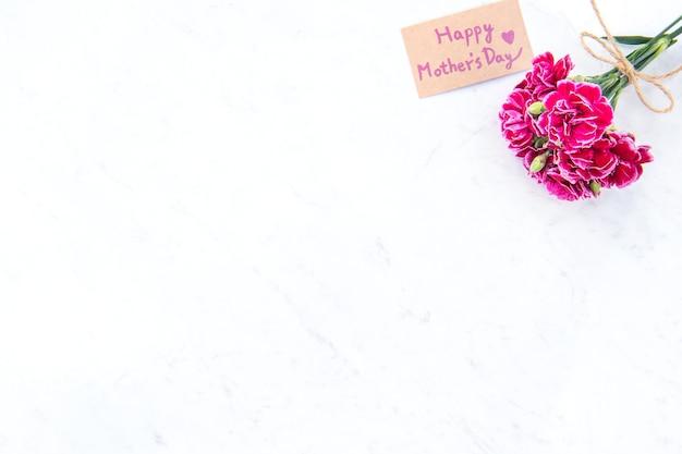 Fotografía del concepto de la idea del día de las madres de mayo - hermosos claveles florecientes atados por un arco con una tarjeta de texto kraft aislada en una mesa moderna y brillante, espacio de copia, endecha plana, vista superior, maqueta