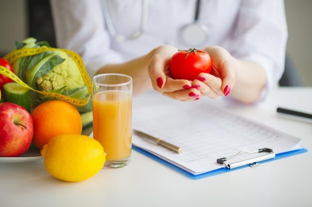 Fotografía conceptual de una mujer nutricionista con frutas en el escritorio