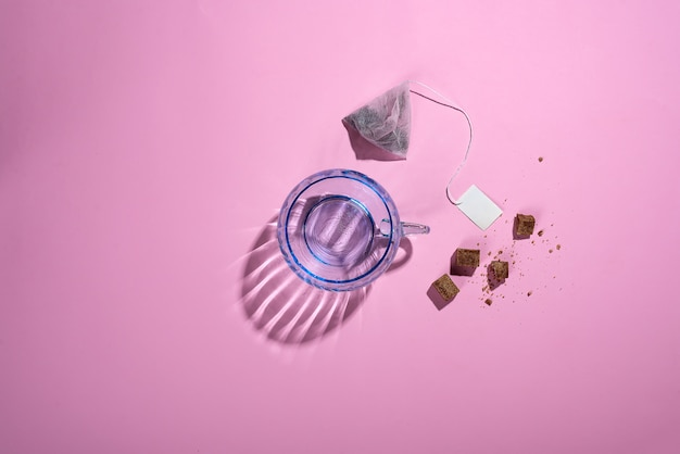 Fotografía creativa con una taza de cristal azul con hermosas sombras reflectantes, una bolsa de té.