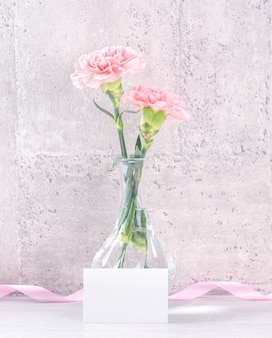 Fotografía de deseos sorpresa de caja de regalo hecha a mano para el día de la madre: hermosos claveles en flor con caja de cinta rosa aislada en el diseño de papel tapiz gris