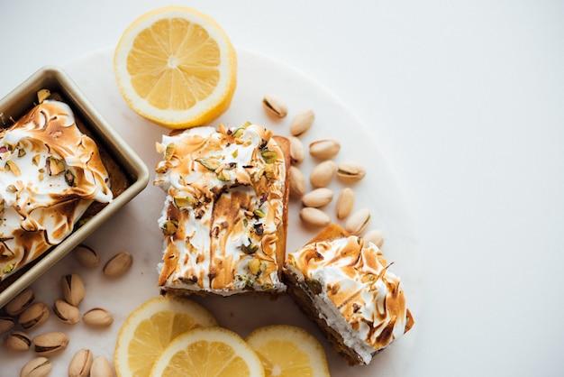 Fotografía general de sabroso pastel postre con nueces y limones en un plato blanco y fondo blanco.