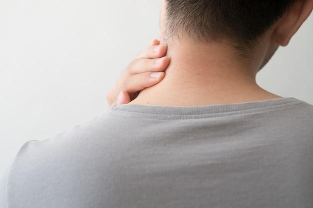 Fotografía de un hombre de espalda con dolor y lesión en el cuello.
