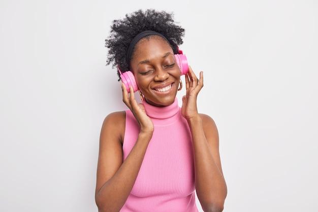 Fotografía en interiores de una encantadora mujer de piel oscura que cierra los ojos por placer, escucha su música favorita, mantiene las manos en los auriculares estéreo de color rosa