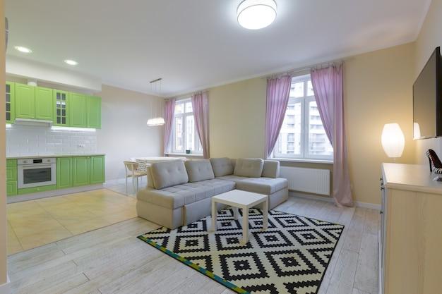 Fotografía de interiores gran sala de estudio con cocina moderna verde