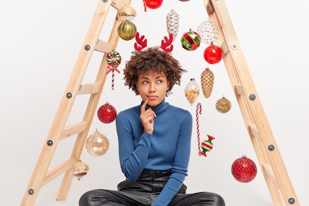 Fotografía en interiores de una mujer de piel oscura pensativa sentada con las piernas cruzadas en el suelo con expresión soñadora hace que las resoluciones de año nuevo sueñen con poses de planes futuros