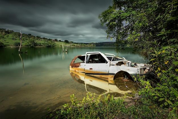 Una fotografía de larga exposición de un automóvil abandonado por un lago