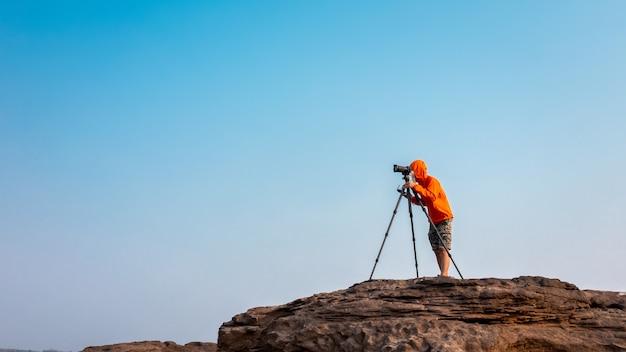 Fotografía de la libertad imágenes de archivo disparando el trípode de la cámara en la roca de la montaña en sam phan bok ubon ratchathani tailandia fondo de cielo azul aislado