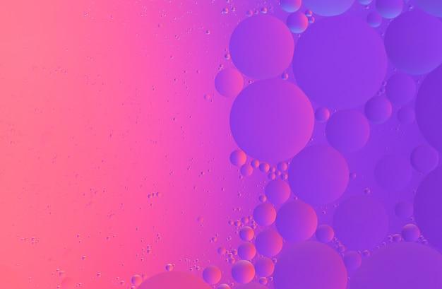 Fotografía macro de aceite sobre agua de fondo degradado de color rosa y violeta abstracto