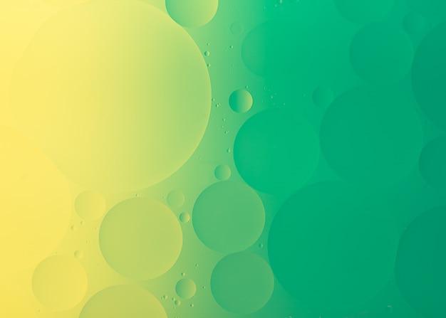 Fotografía macro de aceite sobre agua de fondo degradado de color verde y amarillo abstracto