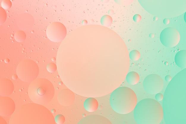 Fotografía macro de aceite sobre agua de fondo degradado de color verde y rosa abstracto
