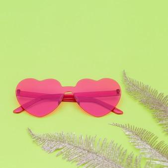 Fotografía de moda de estilo minimalista con gafas en forma de corazón y hojas de palma doradas sobre fondo de papel verde. gafas de sol rosadas modernas. concepto de tendencia de verano. copia espacio