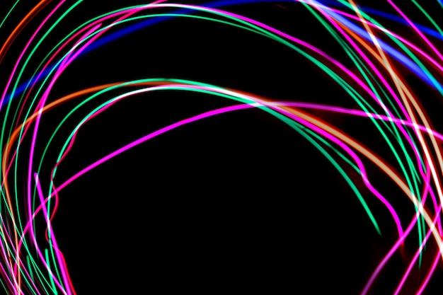 Fotografía de pintura de luz multicolor, remolino y curva de luz azul, verde y roja sobre un fondo negro.