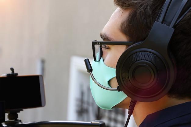 Fotografía en primer plano de un camarógrafo que trabaja al aire libre, con auriculares y micrófono. máscara facial como protección contra el covid en la cara.