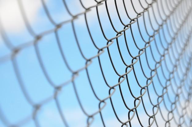 Una fotografía de una red de metal usada como una cerca de posesiones privadas.