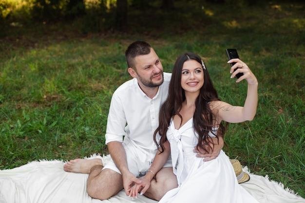 Fotografía de stock de una hermosa pareja en ropa blanca sentada en una manta de picnic. bonita novia con cabello largo castaño en vestido blanco sosteniendo teléfono móvil y tomando selfie.