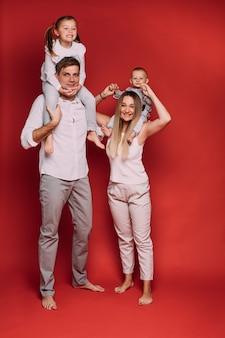 Fotografía de stock de madre cariñosa con hijo y papá con hija sentada sobre los hombros y sonriendo felizmente sobre fondo rojo.
