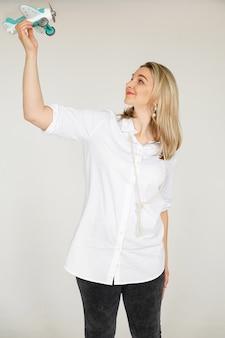 Fotografía de stock de mujer caucásica rubia alegre en camisa blanca y pantalones de mezclilla con cuentas en el cuello volando un avión de juguete en su brazo por encima de la cabeza. concepto de viaje.