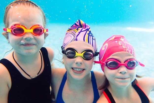 Fotografía submarina de jóvenes amigos en la piscina