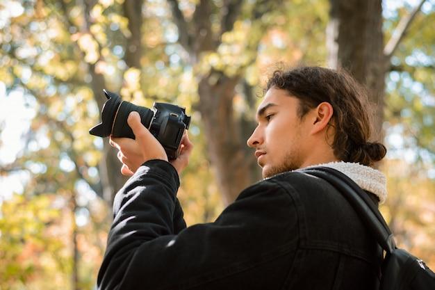 Fotógrafo aficionado de la naturaleza tomando fotos en el bosque de otoño