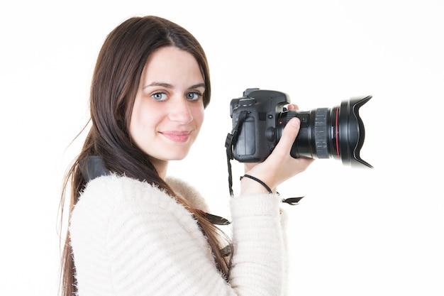 El fotógrafo alegre de la mujer joven toma imágenes con la cámara del dslr
