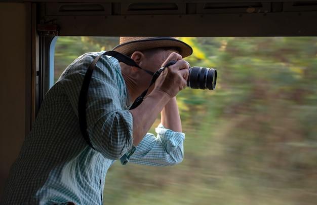 Fotógrafo asiático con sombrero y cámara, toma fotos desde la ventana abierta del tren vintage