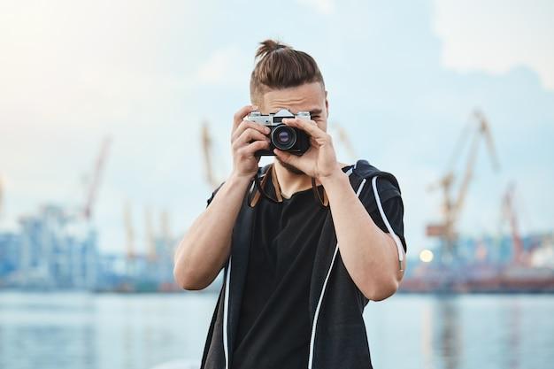 Fotógrafo con cámara vintage tomando fotos cerca del mar, caminando por la ciudad para fotografiar cada momento interesante