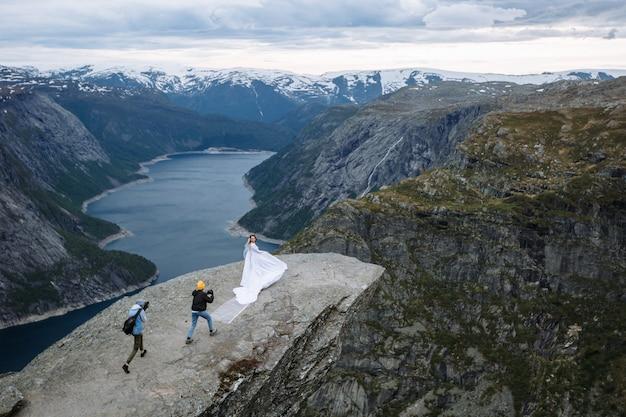 El fotógrafo y camarógrafo toman una foto de los recién casados en un pedazo de roca en noruega llamado la lengua del troll