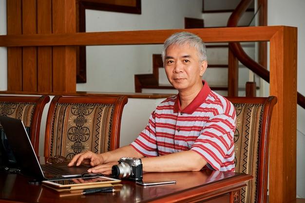Fotógrafo chino trabajando en equipo portátil