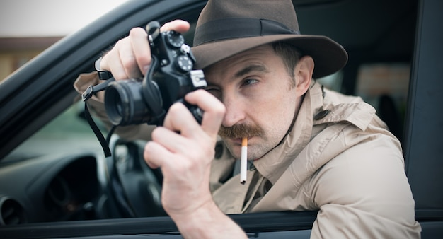 Fotógrafo de espía o paparazzo, hombre usando cámara en su carro.