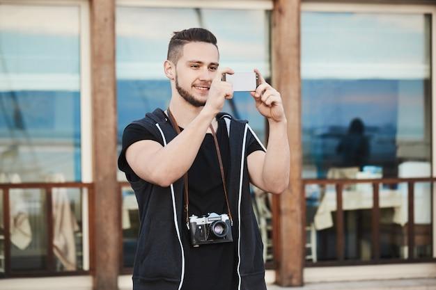 Fotógrafo europeo en ropa de moda tomando fotos en el teléfono mientras usa la cámara en el cuello