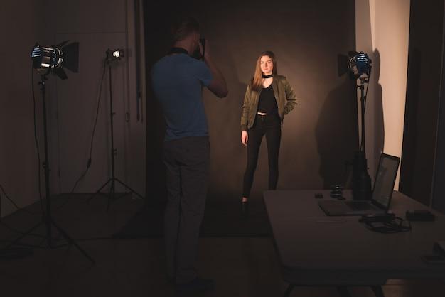 Fotógrafo fotografiando modelo femenino
