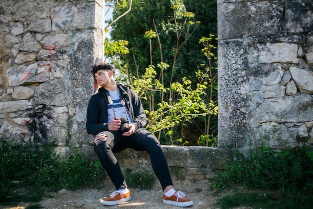 Fotógrafo joven cansado que se sienta en la pared de piedra vieja con sostener la cámara