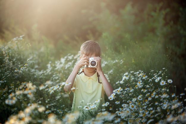 El fotógrafo lindo del muchacho tira en cámara en naturaleza. kid toma una foto en el campo de flores de manzanilla.