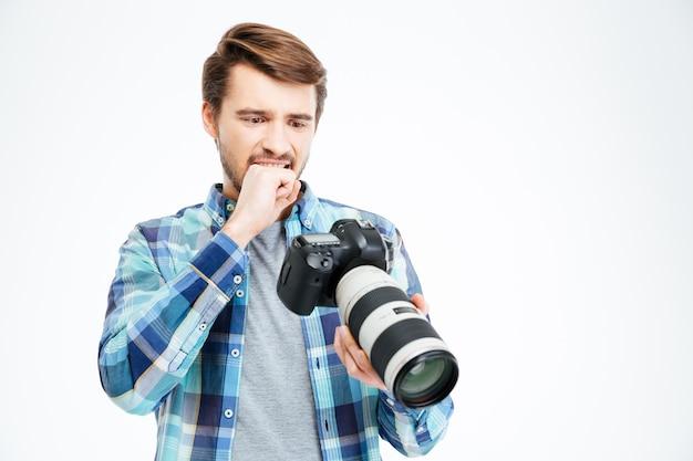 Fotógrafo macho molesto sosteniendo la cámara de fotos aislado sobre un fondo blanco.