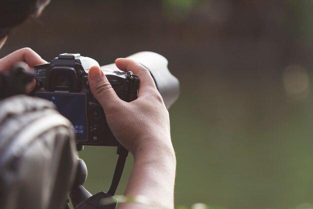 Fotógrafo manejando cámara digital.