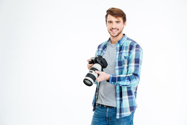 Fotógrafo masculino casual sosteniendo la cámara de fotos aislado sobre un fondo blanco.