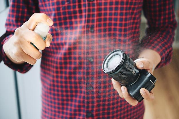 Fotógrafo masculino irreconocible rociando lente de cámara con líquido de limpieza