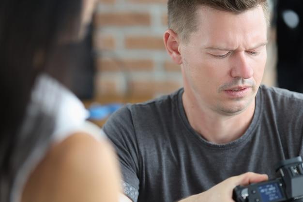 Fotógrafo masculino está mirando la pantalla de la cámara con concentración eligiendo profesión como