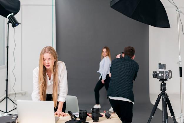 Fotógrafo con modelo y mujer trabajando en la computadora portátil desde la vista
